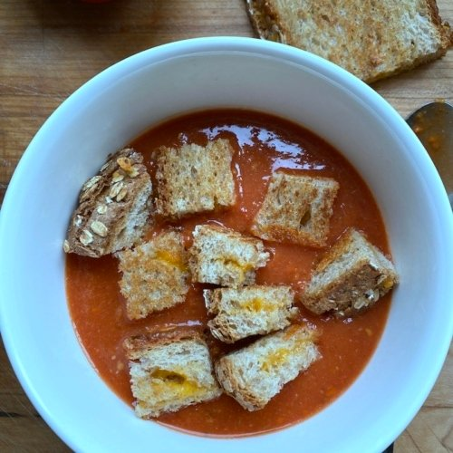 this is a picture of tomato soup with grilled cheese croutons