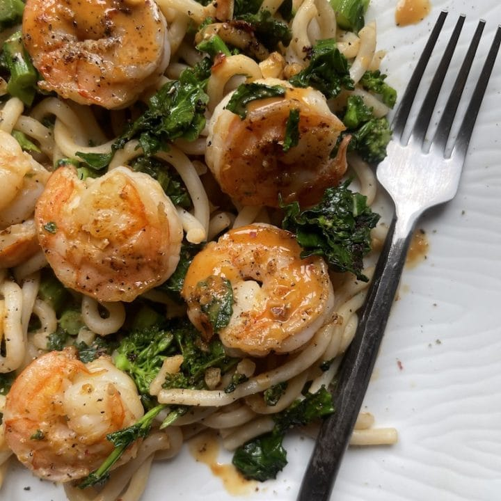 this is a photo of shrimp lo mein with broccoli rabe